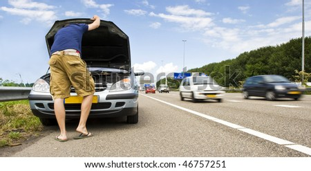 Man staring down at the engine of his stalled car on the hard shoulder of a motorway - stock photo