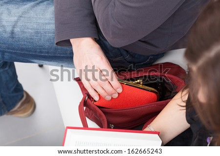 Man stealing a wallet from female purse - stock photo