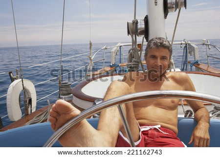 Man steering sailboat with foot - stock photo
