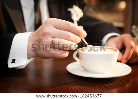 Man stirs sugar in a cup of coffee - stock photo