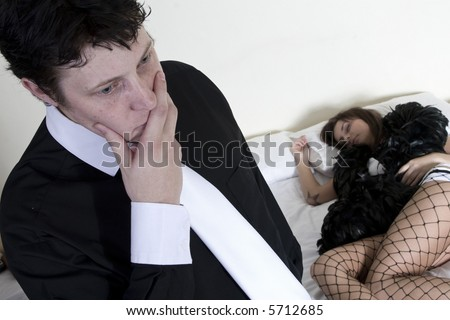 Man stressing about situation with prostitute on the bed behind him - stock photo