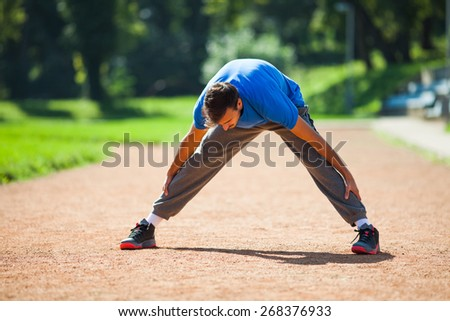 Man stretching body, warming up for jogging - stock photo