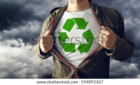 Man stretching jacket to reveal shirt with recycle symbol printed. Concept of environmental consciousness and natural preservation. - stock photo