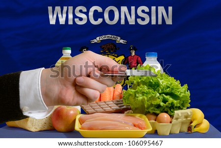 man stretching out credit card to buy food in front of complete wavy american state flag of wisconsin - stock photo