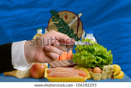 man stretching out credit card to buy food in front of complete wavy american state flag of oklahoma - stock photo