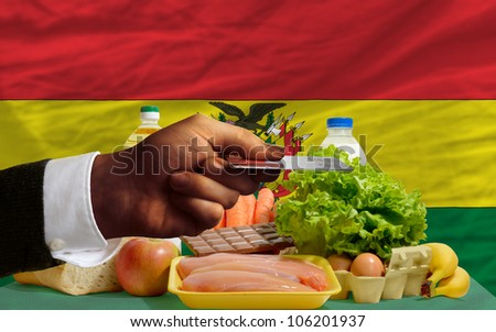 man stretching out credit card to buy food in front of complete wavy national flag of bolivia - stock photo