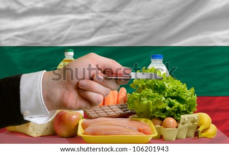man stretching out credit card to buy food in front of complete wavy national flag of bulgaria - stock photo