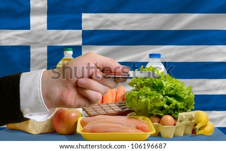 man stretching out credit card to buy food in front of complete wavy national flag of greece - stock photo