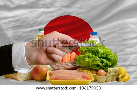 man stretching out credit card to buy food in front of complete wavy national flag of japan - stock photo