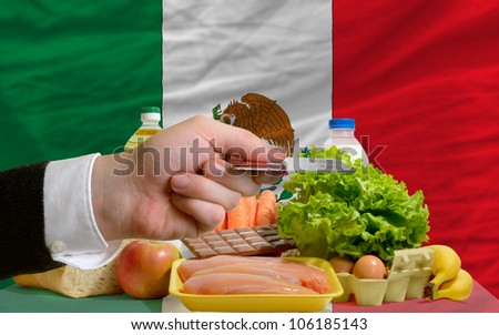 man stretching out credit card to buy food in front of complete wavy national flag of mexico - stock photo