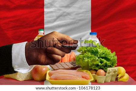 man stretching out credit card to buy food in front of complete wavy national flag of peru - stock photo