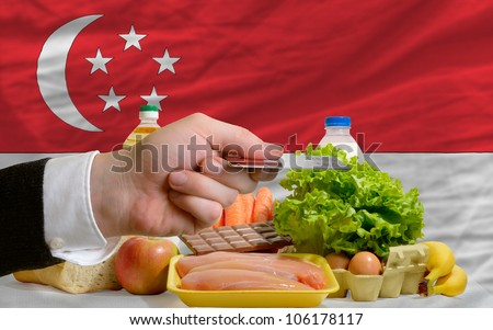 man stretching out credit card to buy food in front of complete wavy national flag of singapore - stock photo