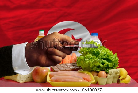 man stretching out credit card to buy food in front of complete wavy national flag of tunisia - stock photo