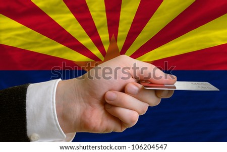 man stretching out credit card to buy goods in front of complete wavy national flag of american state of arizona - stock photo