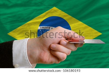 man stretching out credit card to buy goods in front of complete wavy national flag of brazil - stock photo