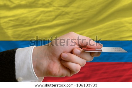 man stretching out credit card to buy goods in front of complete wavy national flag of colombia - stock photo