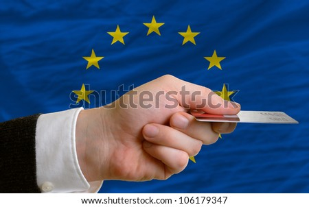man stretching out credit card to buy goods in front of complete wavy national flag of europe - stock photo