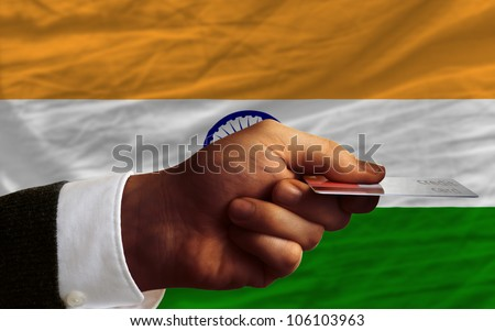 man stretching out credit card to buy goods in front of complete wavy national flag of india - stock photo