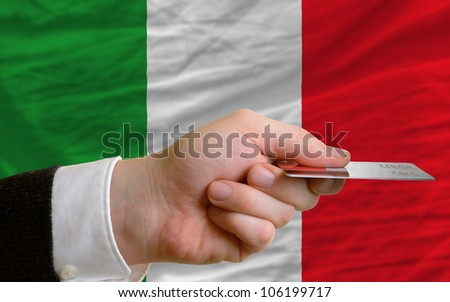 man stretching out credit card to buy goods in front of complete wavy national flag of italy - stock photo