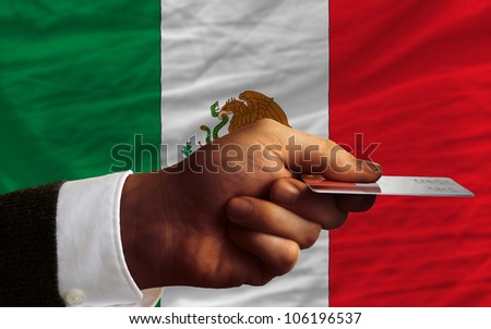 man stretching out credit card to buy goods in front of complete wavy national flag of mexico - stock photo