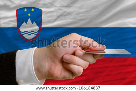 man stretching out credit card to buy goods in front of complete wavy national flag of slovenia - stock photo