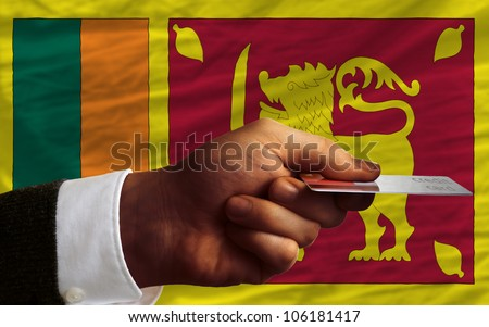 man stretching out credit card to buy goods in front of complete wavy national flag of sri lanka - stock photo