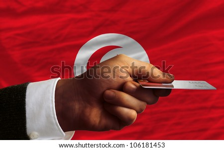 man stretching out credit card to buy goods in front of complete wavy national flag of tunisia - stock photo