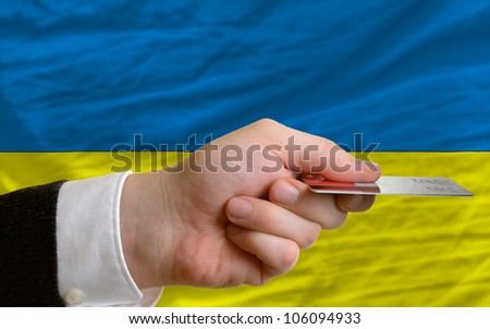 man stretching out credit card to buy goods in front of complete wavy national flag of ukraine - stock photo