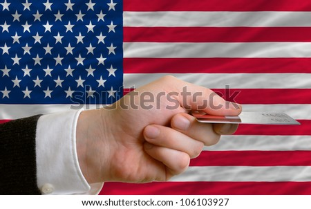 man stretching out credit card to buy goods in front of complete wavy national flag of united states of america - stock photo