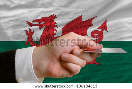man stretching out credit card to buy goods in front of complete wavy national flag of wales - stock photo