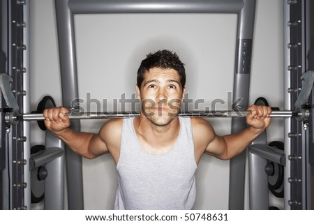 Man struggling to lift Weights on weight machine - stock photo