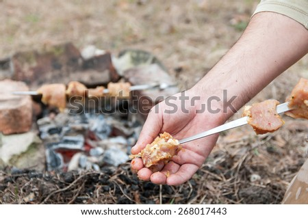 man strung meat  skewer for roasting - stock photo