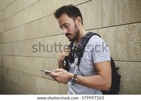 Man student reading information in internet via cell telephone before start lectures in University, bearded hipster guy with rucksack watching video on mobile phone while waiting friends outdoors - stock photo