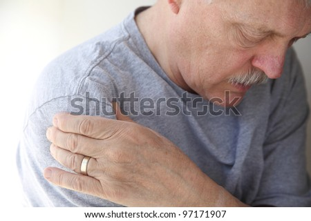 man suffering from aching shoulder - stock photo