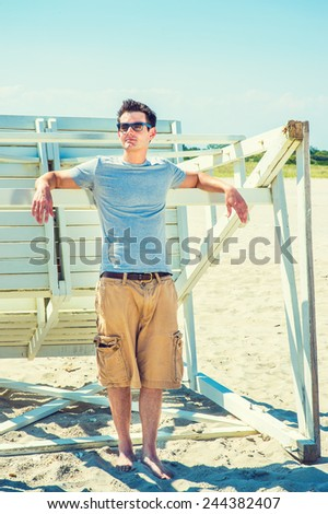 Man Summer Casual Fashion. Wearing a gray t shirt, casual short pants, sunglasses, arms resting on a wooden stick, a young handsome guy is standing by a wooden structure on the beach, looking away.  - stock photo
