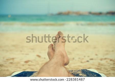 Man sunbathing on lounger. Legs. Vintage effect. - stock photo
