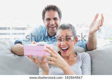 Man surprising his delighted girlfriend with a pink gift on the sofa at home in the living room - stock photo