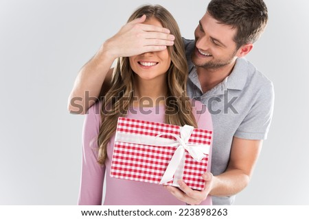 Man surprising his girlfriend with gift on grey background. man covering eyes of girl and standing behind - stock photo