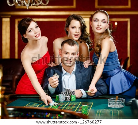 Man surrounded by women plays roulette at the casino club - stock photo