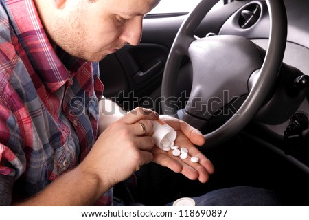 Man swallows drugs in the car - stock photo