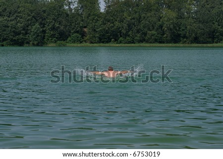 Man swimming in a lake. Healthy lifestyle. - stock photo
