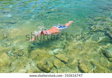 Man swimming in the clear water of sea - stock photo