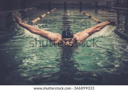 Man swims using breaststroke technique  - stock photo