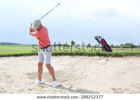 Man swinging at golf course against sky - stock photo