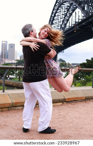 Man swings his girlfriend through the air in front of Sydney Harbour Bridge - stock photo