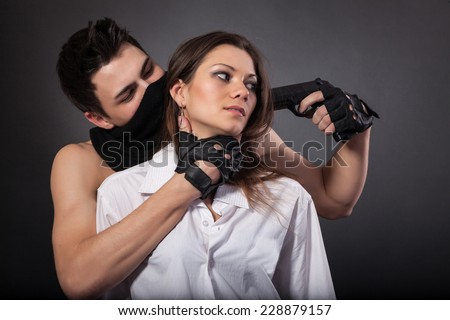 Man take a beautiful woman as a hostage isolated on a white background - stock photo