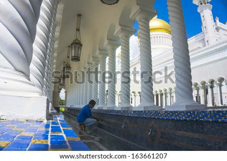 Man takes ablution at Masjid Sultan Omar Ali Saifuddin Mosque in Bandar Seri Begawan, Brunei Darussalam. Brunei plan to implement sharia law soon. - stock photo