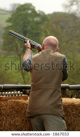 Man takes aims and fires at the clay pigeon - stock photo