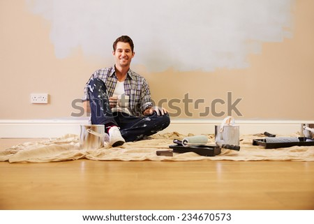 Man Taking A Break Whilst Decorating Room - stock photo