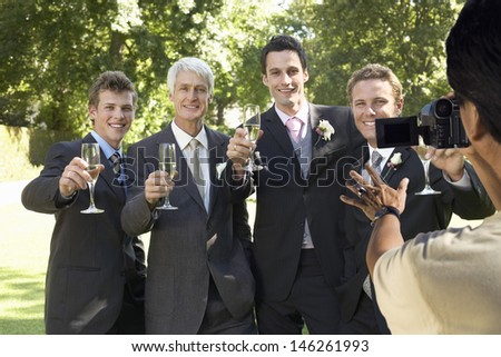 Man taking a picture of five men toasting with wine glasses at wedding party - stock photo